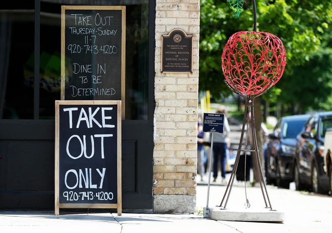 "Signs outside Cedar Crossing restaurant state ""Take out only"" and ""Dine in to be determined"" on June 12, 2020, in Sturgeon Bay, Wis."