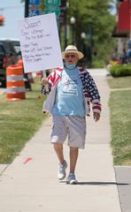 """Singing """"America the Beautiful"""" as he starts out, Connie Quinn, of Marion Township, walks from the historic Livingston County courthouse in Howell toward Brighton Wednesday, June 17, 2020 in support of Gov. Gretchen Whitmer's policies regarding the COVID-19 pandemic."""