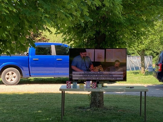 A television displaying a church service is set up in Regina Roberts' yard in Pinckney.