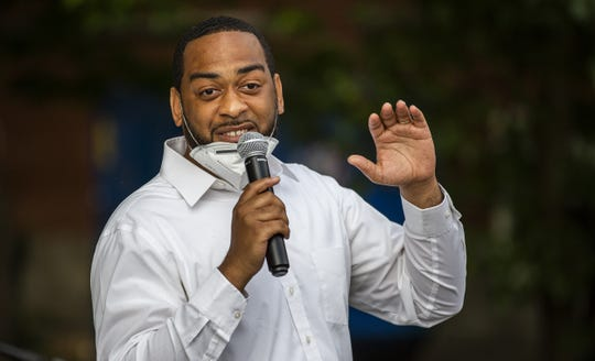 State Rep. Charles Booker gestures while speaking to an enthusiastic crowd at Highland Coffee Company on Bardstown Road on Wednesday.