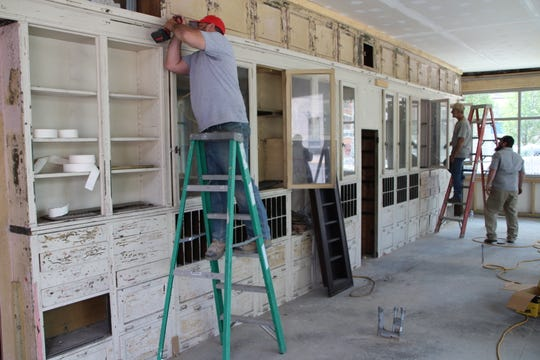 Crews install vintage cabinets inside the Center Street Market on Tuesday, June 16, 2020. The cabinets are just one of many antique items that will be located inside the grocery store at the corner of Center and Main streets in downtown Marion. Center Street Community Health Center is developing the market.