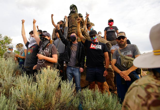Demonstrators climb the statue of Don Juan de Oñate in Old Town in Albuquerque, N.M., while an armed member of the New Mexico Civil Guard stands by during a protest calling for the removal of the likeness of the controversial New Mexico explorer Monday, June 15, 2020.