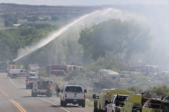 Firefighters work the site of the Arroyo Fire alongside County Road 4800 on July 1, 2019