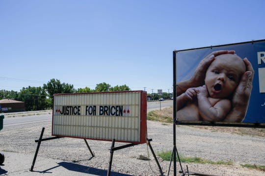 """A """"Justice for Bricen"""" sign is displayed Friday, Sept. 14, 2018, adjacent to a shopping center on N.M. Highway 516 in Flora Vista."""