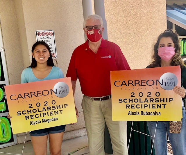 Executive Director Ricardo Loretta gives yard signs to two students from Palo Verde High School in Blythe.