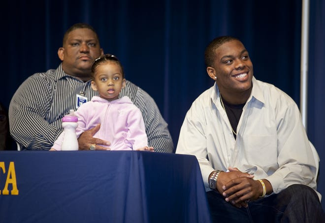 ARIZONA REPUBLIC PHOTO BY MARK HENLE - 01/27/2009 - Desert Vista football player Devon Kennard (right, CQ) is introduced at a press conference Tuesday morning were he announced he will be attending USC.  Sitting next to Devon is his father, Derek Kennard and his niece, Sa-Rae Kennard (both CQ).