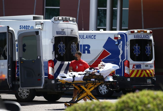 A person is brought to a medical transport vehicle from Banner Desert Medical Center as several transports and ambulances are shown parked outside the emergency room entrance, Tuesday, June 16, 2020, in Mesa.