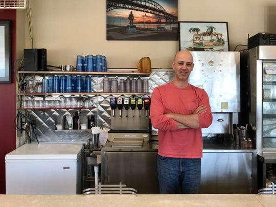 Chris Smith, owner of Cavis Grill in downtown Port Huron, poses for a photo behind the diner's bar. The business is participating in the MI Local Biz program to get a matching grant of up to $5,000 for coronavirus relief funds.
