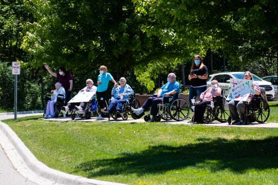 Regency-on-the-Lake residents wave to cars during a drive-by parade Wednesday, June 17, 2020, in front of the Fort Gratiot nursing home.