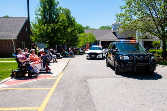 Regency-on-the-Lake residents wave to patrol cars during a drive-by parade Wednesday, June 17, 2020, in front of the Fort Gratiot nursing home.