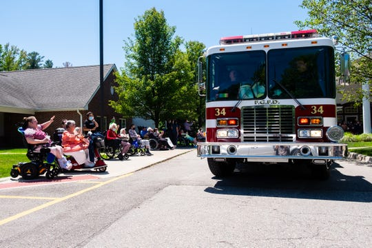 Regency-on-the-Lake residents wave to a Fort Gratiot firetruck during a drive-by parade Wednesday, June 17, 2020, in front of the Fort Gratiot nursing home.