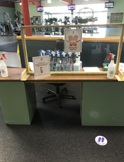 The wellness center desk is stocked with cleaning and disinfectant supplies for people to use when using the gym.