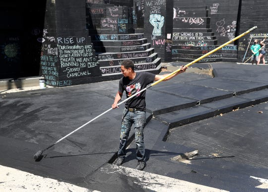 Local Rochester, N.Y. artist Shawn Dunwoody and  volunteers,  paint the amphitheater at Martin Luther king Jr. Park,  to allow visitors to write messages as part of the Black Lives Matter movement.