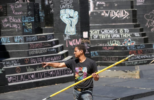 Local artist Shawn Dunwoody directs some volunteers who are helping him paint the amphitheater at Martin Luther king Jr. Park, black, to allow visitors to write messages as part of the Black Lives Matter movement.