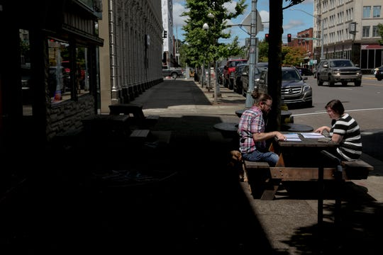 Brian Mosher and Shelly Jackman sit outside at Taproot in Salem, Oregon, on Wednesday, June 17, 2020. The city of Salem is closing streets downtown to allow for more outdoor seating option.