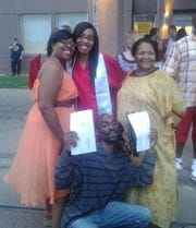 Lazerick Grant stands with family after a graduation ceremony.`