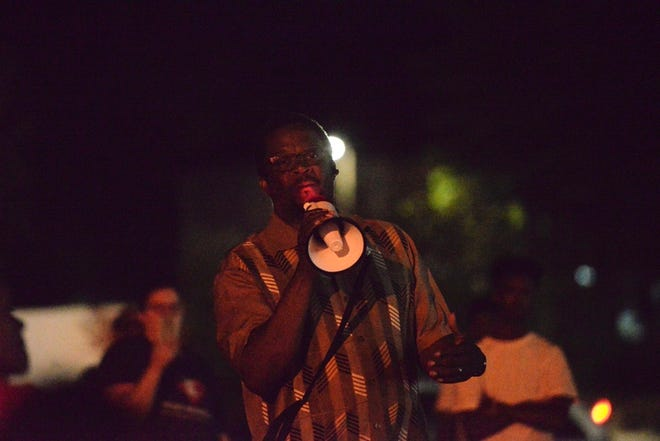 The Rev. James Alberts of Higher Ground Church of God in Christ speaks through a megaphone to a peaceful crowd gathered at Ninth Avenue South and University Drive on Tuesday, June 16, 2020.