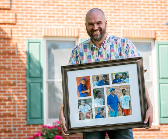 Holland Webb holds a photo collage of his two sons Geoffrey and John Paul.