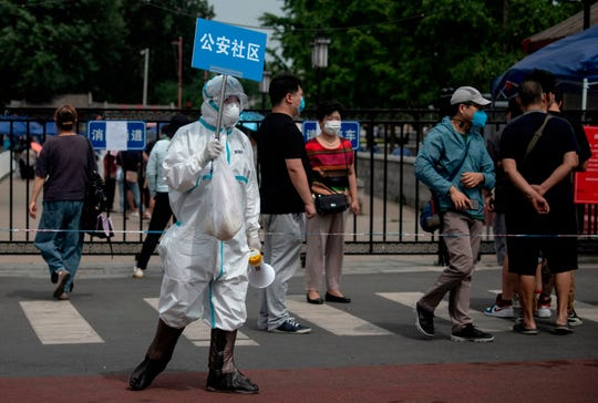 A medical worker in full protective gear holds up a sign to assist people who live near or who have visited the Xinfadi Market, a wholesale food market where a new COVID-19 coronavirus cluster has emerged, as they arrive for testing in Beijing on June 17, 2020.