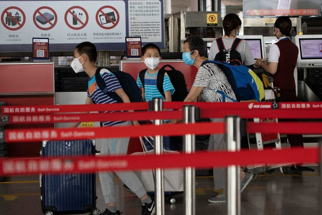Passengers wearing masks to curb the spread of the coronavirus check in at the Beijing Capital Airport terminal 3 in Beijing on Wednesday, June 17, 2020. The Chinese capital on Wednesday canceled more than 60% of commercial flights and raised the alert level amid a new coronavirus outbreak, state-run media reported.