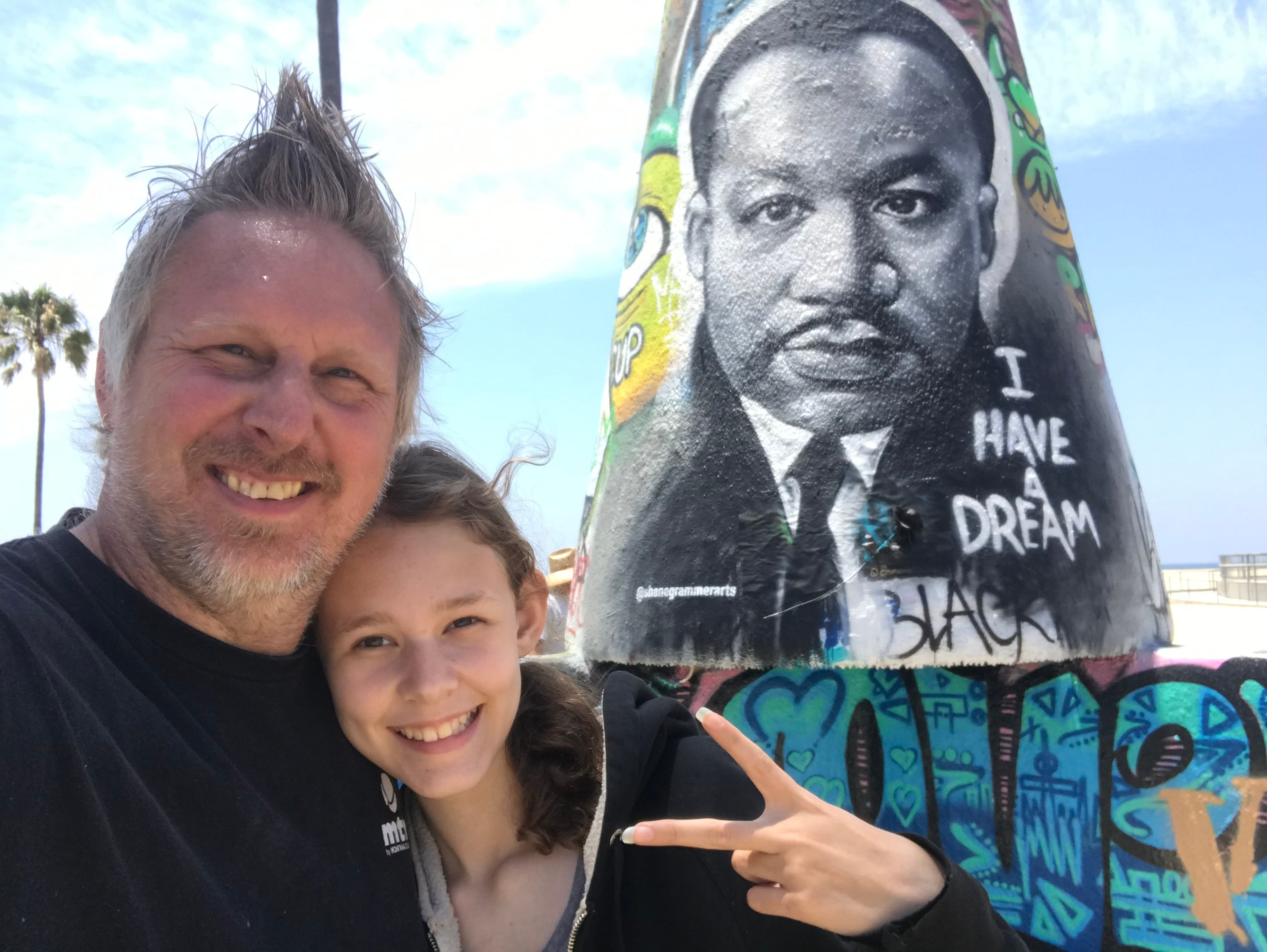 Artist Shane Grammer poses with his daughter, Elliana, in front of his mural of Martin Luther King, Jr. in Venice Beach.