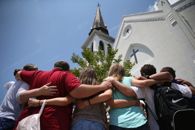 """A church youth group from Dothan, Ala., prays in front of the Emanuel AME Church in July 2015, a month after a mass shooting in Charleston, S.C. Visitors gathered at a makeshift shrine in front of the church in a show of faith and solidarity with """"Mother Emanuel,"""" as the church is known. Nine people were killed by white supremacist Dylann Roof, who was sentenced to death for the murders."""