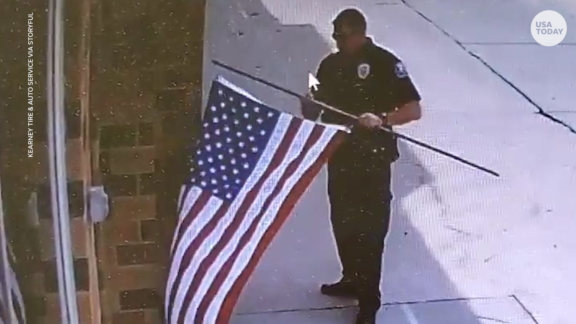 Police officer stops to fix fallen American flag outside of local business