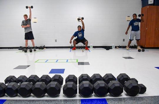 Powdersville High School football players Josh Davis, left, Trez Fowler, and Xavier Fowler lift weights during practice at the school in Powdersville Thursday, June 18, 2020.