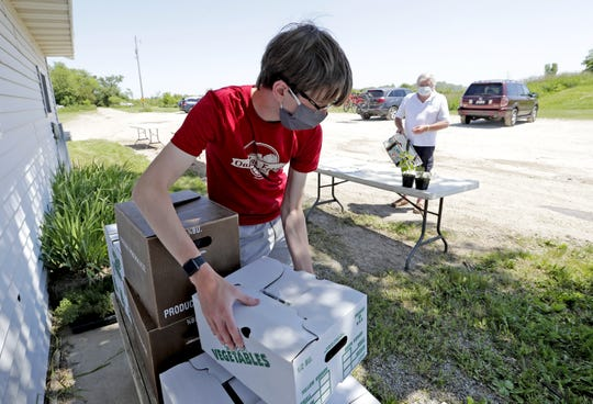 Employee Will Ranger transfers an order of produce for curbside pick up to Phil Johnson of Neenah at Oakridge Farms Tuesday, June 16, 2020, in Neenah, Wis. Due to COVID-19 customers are not allowed to pick their own strawberries this season.