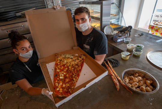 Angela Andrianopoulos and Danny Rios show off the Megaslice, a pizza and calzone combination topped with breaded chicken, tomato sauce and basil. The pizza is on the menu at Joe's Rotisseria in Asbury Park.