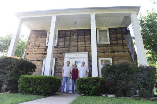 Chuck Richard, Darla Donnenwirth and Mike Donnenwirth stand in front the two-story log home that was built in 1821 and uncovered this spring along Marion Road in Bucyrus.