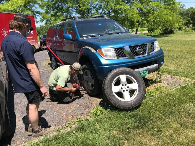 Timely Tire technician Jason Kimball changes a tire on Monica Rugg's truck in South Hero while Ari Moskowitz watches on Tuesday, June 16, 2020.