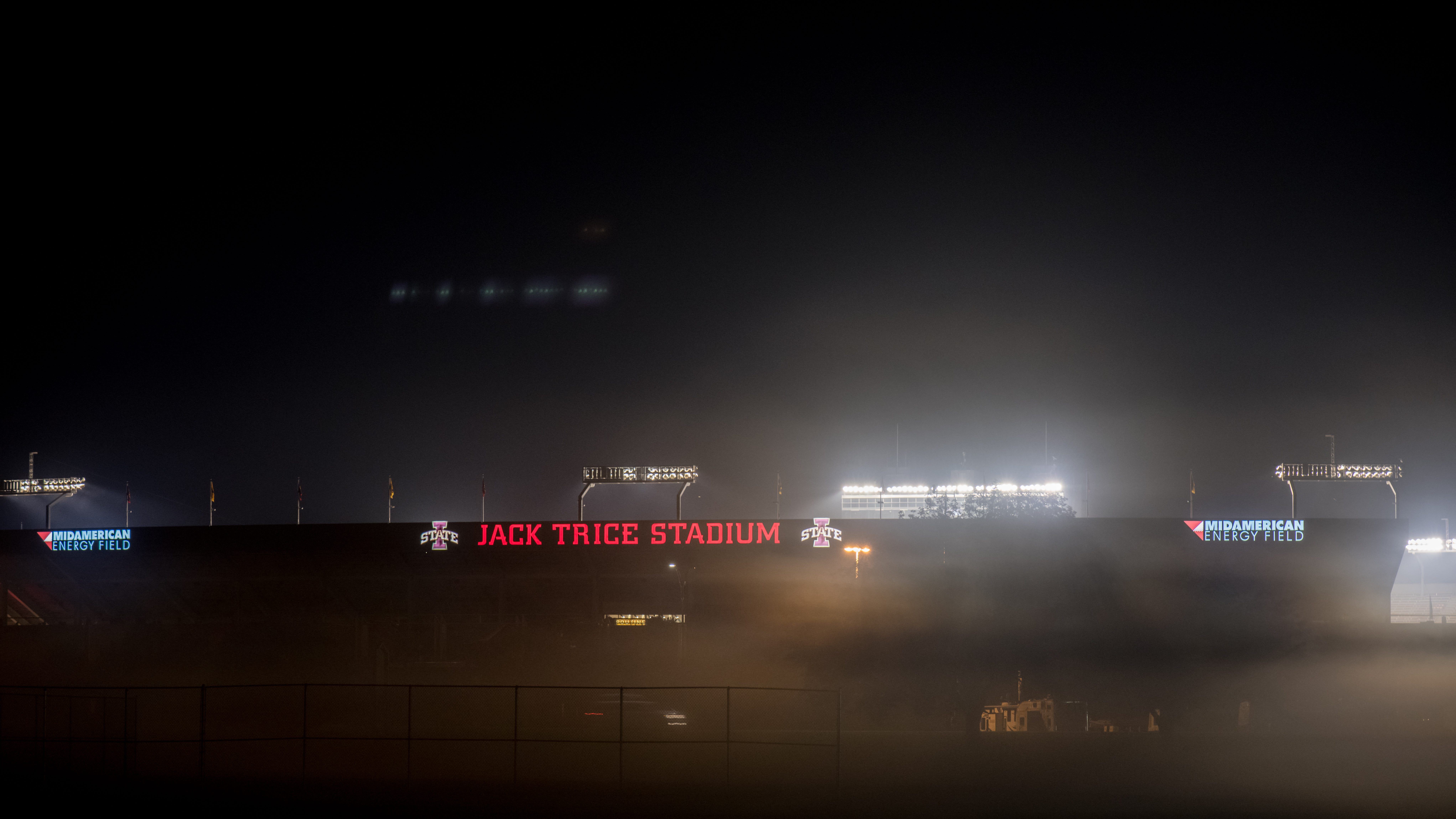The marquee of Jack Trice Stadium, the lone FBS stadium named after a Black man, shines on a misty night.