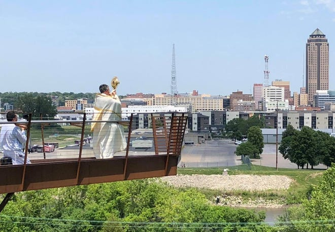 Msgr. Chiodo is shown blessing Des Moines and the state of Iowa June 18, 2020 from the EMC outlook in McRae Park. Chiodo prayed for peace and mutual respect, especially as regards race, and for healing from the COVID-19 pandemic.   Chiodo was born and raised in Des Moines. After graduating from St. Anthony grade school and Dowling High School, he attended Conception Seminary in Missouri in 1974. He was awarded a Master of Arts degree in Moral Theology from St. Thomas Seminary in Denver, Colorado and was ordained in 1976. He serves St. Anthony Catholic Church in Des Moines.