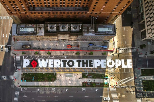 """The """"Power to the People"""" street mural on Woodward Avenue in downtown Detroit will be officially unveiled during a Juneteenth ceremony Friday. The mural was created by Hubert Massey and is being painted by teenage students from the Detroit area."""
