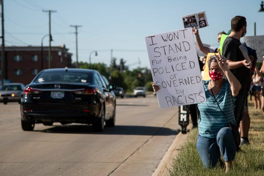 Liz Scutchfield of Shelby Township stands on one knee as she protests Shelby Township police chief Robert Shelide on Van Dyke Avenue outside of Shelby Township Municipal Offices in Shelby Township on June 17, 2020.