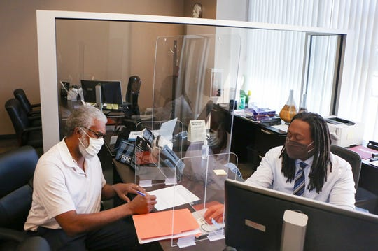 Phares Noel, 64, of West Bloomfield, does some paperwork at First Independence Bank with Derek Boggon, assistant branch manager at the First Independence Bank on Wednesday, June 17, 2020.