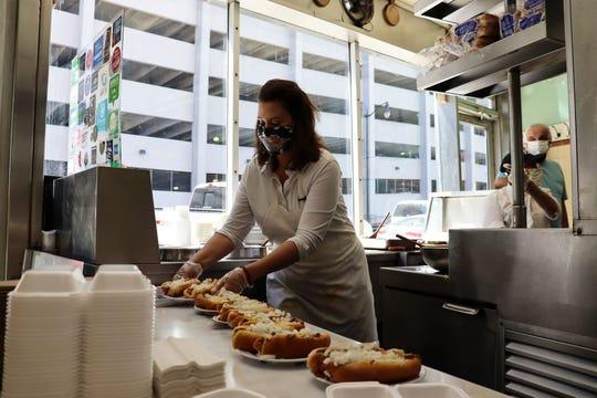 Gov. Gretchen Whitmer serves coney dogs at Lafayette Coney Island in Detroit on Thursday, June 18, 2020.