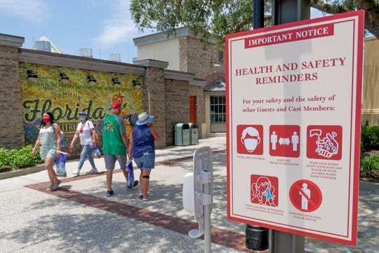 In this June 16, 2020, file photo, signs remind patrons to wear masks and other protocols because of the coronavirus pandemic as they stroll through the Disney Springs shopping, dining and entertainment complex in Lake Buena Vista, Fla.