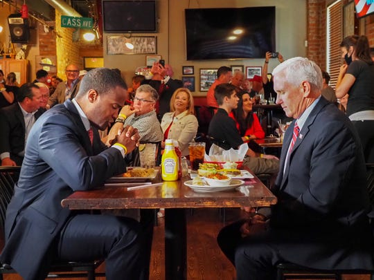 Republican U.S. Senate candidate John James and Vice President Mike Pence pray before eating burgers for lunch at the Engine House restaurant in Mt. Clemens, Mich. on Thursday, June 18, 2020.