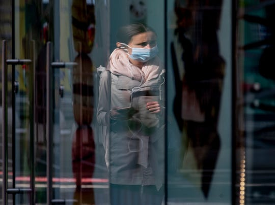 A woman wearing a face mask is reflected in a shop window at the central train station in Frankfurt, Germany, Thursday, June 18, 2020.