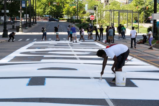 "In this Wednesday, June 17, 2020 photo, Detroit public schools students and youths with Detroit Heals Detroit, a social justice organization that helps Detroit youths who have suffered trauma, paint a mural on Woodward Ave in Detroit. The mural, funded by the Knight Foundation and Bedrock, will spell out ""Power to the People""."