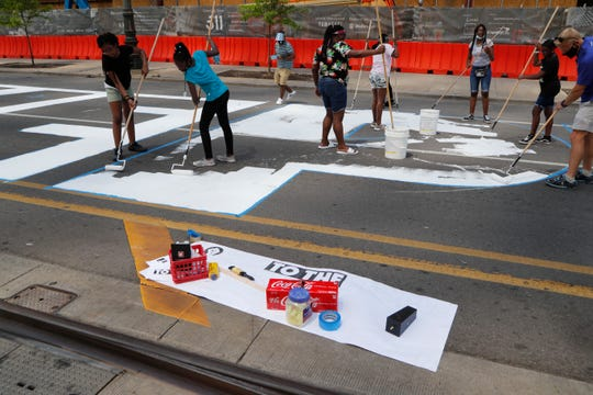 "In this Wednesday, June 17, 2020, photo, Detroit public schools students and youths with Detroit Heals Detroit, a social justice organization that helps Detroit youths who have suffered trauma, paint a mural on Woodward Ave in Detroit. The mural, funded by the Knight Foundation and Bedrock, will spell out ""Power to the People""."