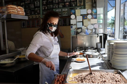 Governor Gretchen Whitmer serves coney dogs at Lafayette Coney Island in Detroit, Thursday, June 18, 2020.