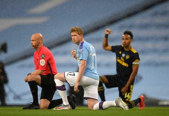 Manchester City's Kevin De Bruyne takes a knee in support of the Black Lives Matter movement before the English Premier League soccer match between Manchester City and Arsenal at the Etihad Stadium in Manchester, England, Wednesday, June 17, 2020.