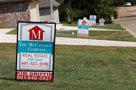 In this Sept. 25, 2019 file photo, a realty company's signs rest on several lawns in front of newly constructed houses in Brandon, Miss..
