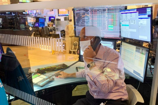 Meric Greenbaum, with IMC, is seen behind one of the newly installed plastic barriers at trading posts on the floor of the New York Stock Exchange, as specialists returned to the partially reopened trading floor, Thursday, June 18, 2020.