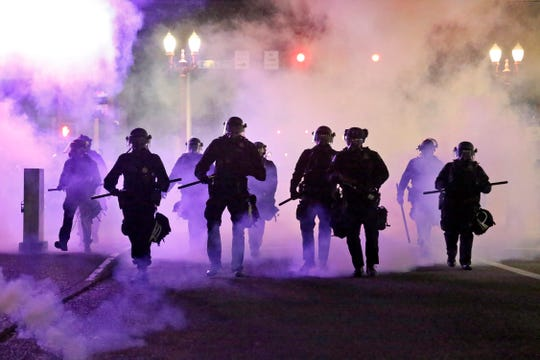 FILE - In this March 29, 2020, file photo, police officers walk enveloped by tear gas in Portland, Ore. City commissioners in Portland voted Wednesday, June 17, 2020 to cut nearly $16 million from the Portland Police Bureau's budget in response to concerns about police brutality and racial injustice.