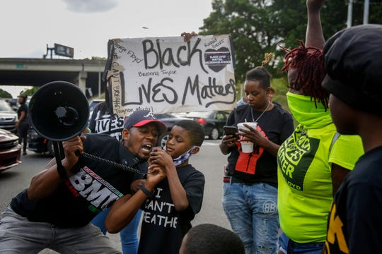 "Protesters yells ""Black Lives Matter"" in the street near a Wendy's restaurant on Wednesday, June 17, 2020 in Atlanta. The restaurant was where Rayshard Brooks was shot and killed by police."