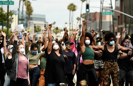 In this June 5, 2020, file photo, protesters raise their fists during a rally in support of Black Lives Matter outside the Academy of Motion Picture Arts & Sciences in Beverly Hills, Calif.